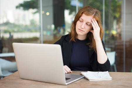 Peinzende vrouw die laptop in diepe gedachten bekijkt Stockfoto - 92321935