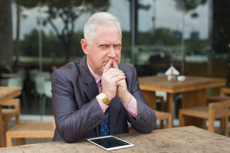 Gloomy Business Leader with Tablet in Street Cafe Stock Photo