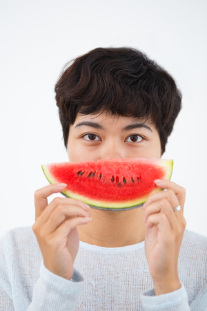 Playful woman eating watermelon for refreshment Stock Photo