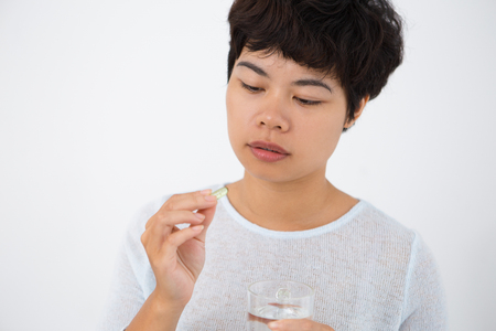 Worried Asian woman taking pill to get rid of pain Stock Photo