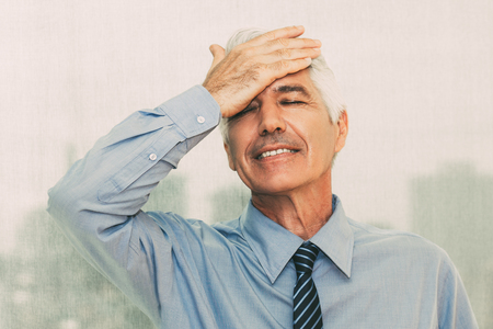 Forgetful senior businessman slapping forehead