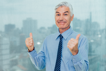 Successful senior businessman showing thumbs up