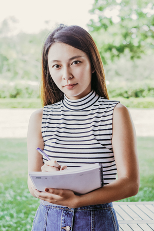 Portrait of serious female student with copybook