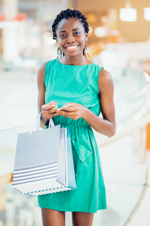 Portrait of happy young woman in shopping mall