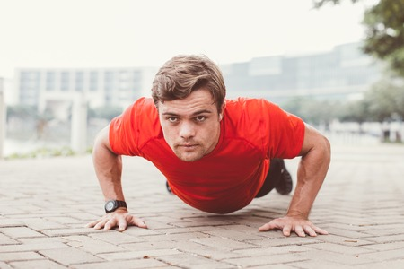 Determined Sporty Man Doing Push-ups on Pavement Stock Photo