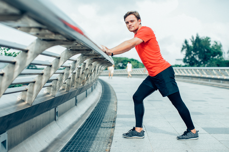 sporty man stretching calf and leaning on railing stock photo