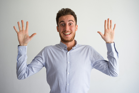 Cheerful businessman raising arms to surrender