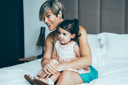 Curious mother and daughter watching tv in bedroom