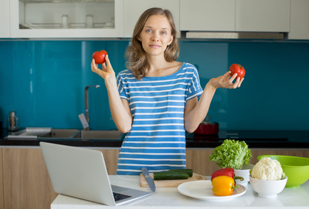 Content Caucasian Girl Cutting Vegs in Kitchen