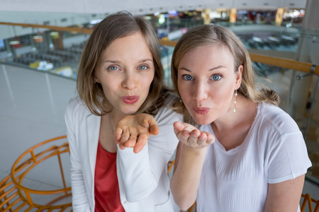 Two Content Girlfriends Sending Air Kiss to Viewer Stock Photo