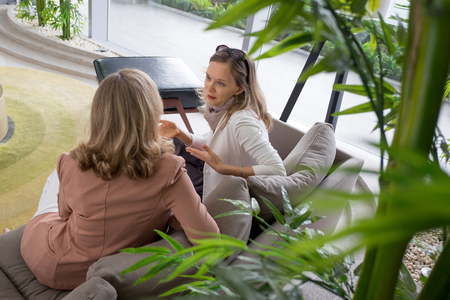 Two Young Women Chatting in Lounge Standard-Bild