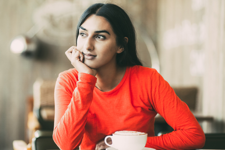 Dreamy Indian girl sitting at table in restaurant