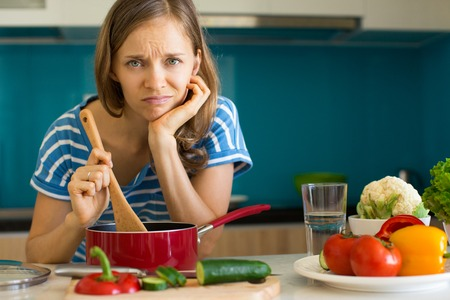 Dissatisfied Woman Cooking Dish in Sauce Pan