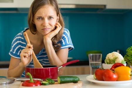 Niezadowolona kobieta gotująca danie w sosie patelni