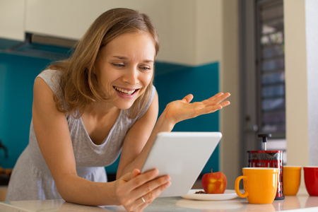 Smiling Lady Browsing on Tablet in Kitchen Stock Photo