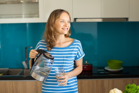 Smiling Lady Pouring Water from Kettle into Glass