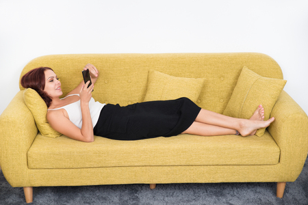 Smiling beautiful businesswoman relaxing on sofa Stock Photo