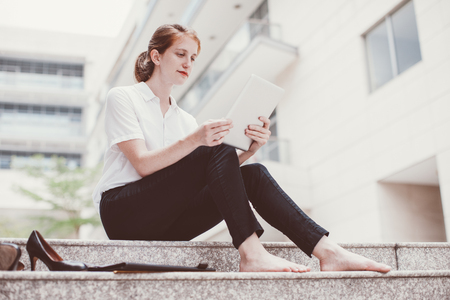 Serious Female Student Using Tablet on Stairs