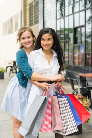 Two Beautiful Diverse Women Shopping and Embracing Stock Photo