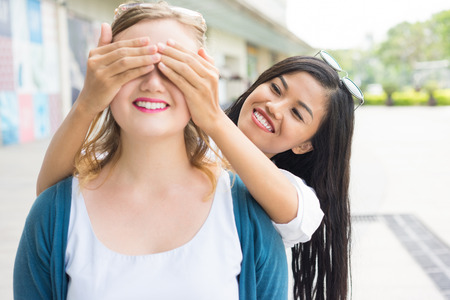 Asian Girl Covering Girlfriend Eyes Outdoors Stock Photo