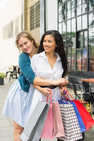 Two Beautiful Diverse Women Shopping and Hugging Stock Photo