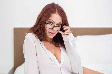 Positive sexy girl adjusting eyeglasses