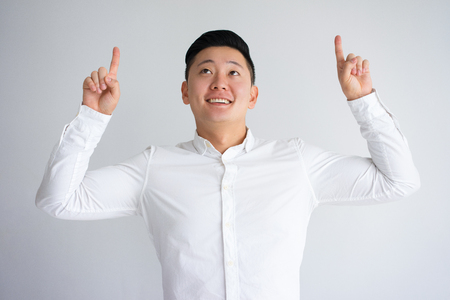 Happy Asian Guy Looking and Pointing Fingers Up Фото со стока