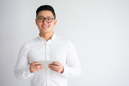 Happy Young Asian Man Holding Tablet