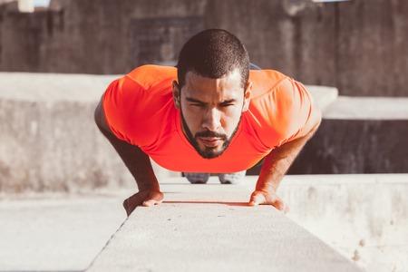 Determined Sporty Man Doing Push-ups on Parapet Stock Photo