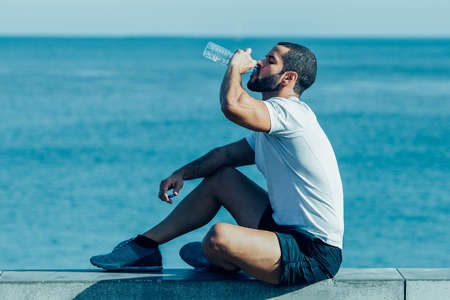 Sporty Man Drinking and Sitting on Parapet at Sea
