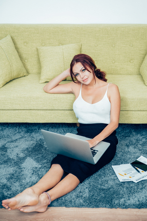 Smiling young woman sitting with laptop on floor