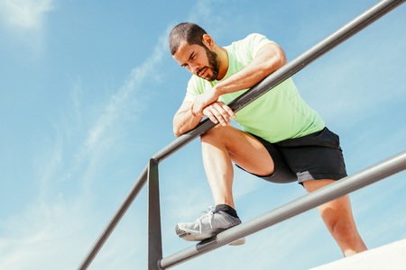 Tired Sporty Man Relaxing and Leaning on Railing Stock Photo