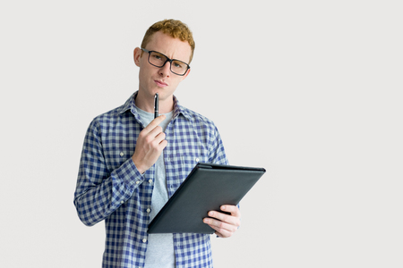 Puzzled Red Haired Young Man Holding Folder