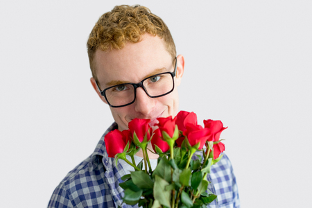 Smiling Red Haired Young Man with Bunch of Roses