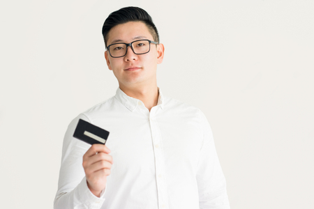 Confident Korean businessman using credit card
