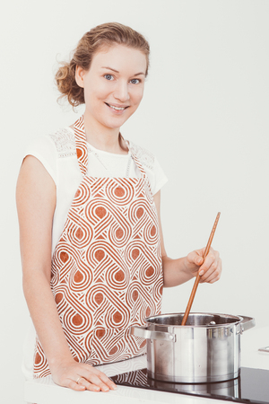Cheerful attractive housewife stirring soup in pot