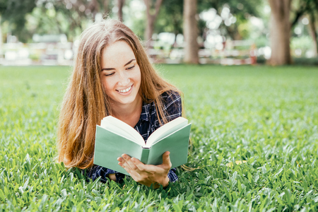 Smiling dreamy girl reading romance book Stock Photo