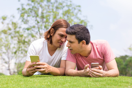 Men Using Smartphones, Chatting and Lying on Lawn
