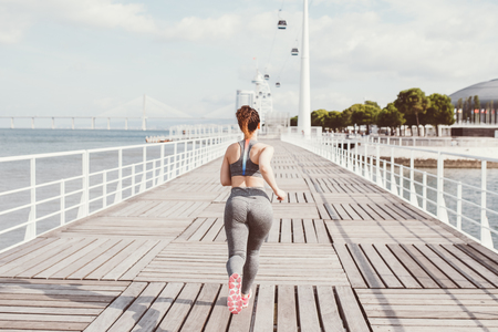 Young attractive woman wearing sportswear, training and jogging on bridge with river and city in background. Back view.