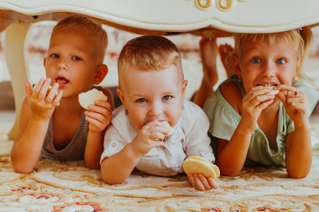 Little Boys and Girl Eating Cookies Under Table Foto de archivo
