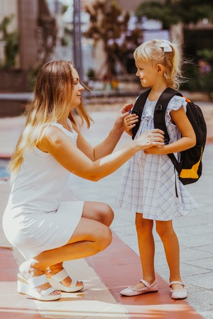 Mother Adjusting Daughter Clothes Before School