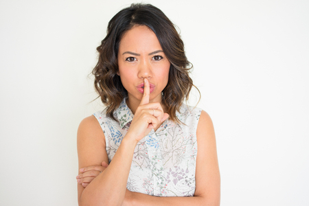 Portrait of young Asian woman with finger on lips Stock Photo