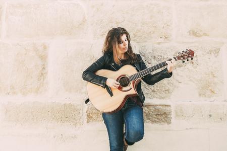 Pensive Female Street Musician Playing Guitar 스톡 콘텐츠