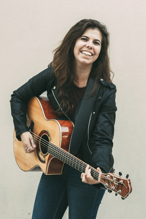 Smiling Young Woman Playing Guitar