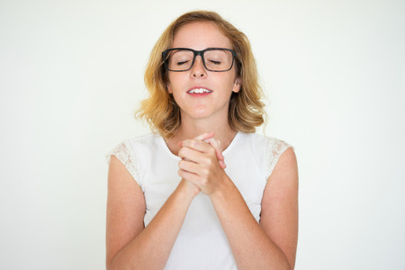 Inspired woman closing eyes to make wish Stock Photo