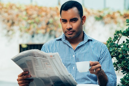 Handsome Hispanic Man with Coffee and Newspaper Stock Photo