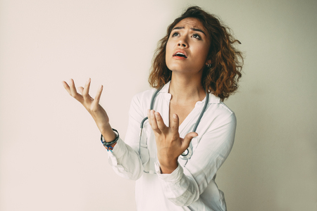 Portrait of disappointed female doctor praying