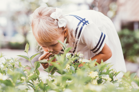 Little Girl Bending Down to Smell Flowers Outdoors