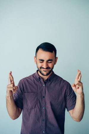 Focused Man Showing Crossed Fingers Gesture Foto de archivo