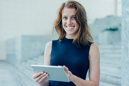 Smiling Pretty Lady Using Tablet Computer Outdoors